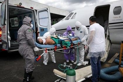 Otaviano Batista, de 67 años, un paciente que sufre la enfermedad coronavirus (COVID-19), es ayudado por trabajadores de la salud al salir de un avión de la UCI, que llega de Tabatinga a Manaos, Brasil, el 18 de mayo de 2020. REUTERS/Bruno Kelly