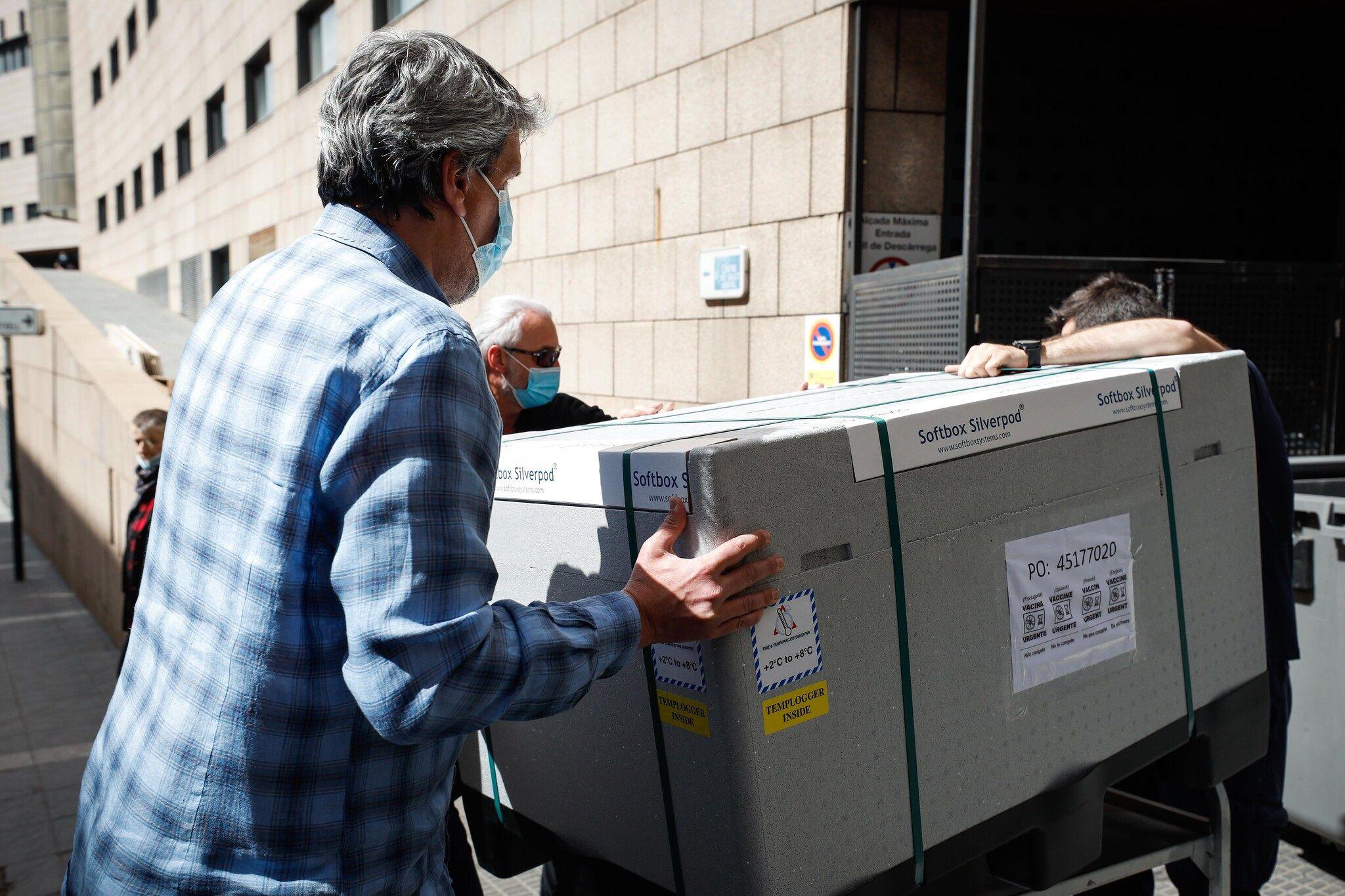Operarios trasladando un cargamento de vacunas.