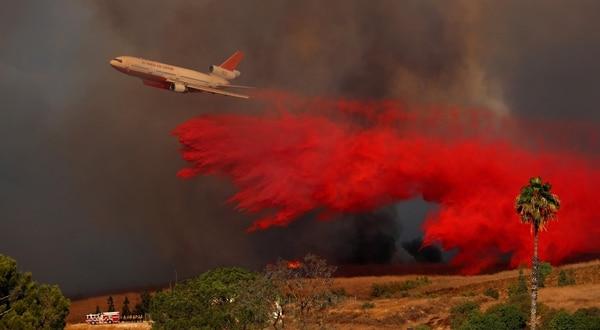 Un avión hidrante esparce retardante de fuego en Orange, California, para impedir el avance del fuego (Reuters)