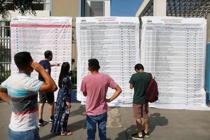 Votantes revisan las listas de candidatos en un colegio electoral en Lima (Reuters)