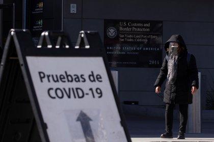 Una mujer en Tijuana, México espera en una línea para hacerse una prueba de COVID-19 antes de ingresar a EEUU -  REUTERS/Mike Blake