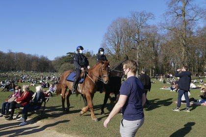En esta imagen de archivo del domingo 28 de febrero de 2021 la policía patrulla mientras gente disfruta del clima soleado en el parque Bois de la Cambre, en Bruselas. (AP Foto/Sylvain Plazy, Archivo)