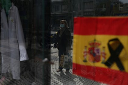 Una mujer con una mascarilla, afuera de una farmacia que colgó una bandera española en Madrid (Reuters)