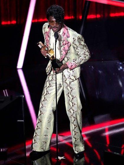 """Lil Nas X se alzó con el premio a la """"mejor canción hot del 100"""" gracias a su popular hit titulado """"Old Town Road"""", el cual fue realizado en conjunto con el mítico Billy Ray Cyrus. El artista optó por un estilo inspirado en los 80: un traje Gucci verde claro con estampado de piel de serpiente y anillos Bvlgari (Foto AP / Chris Pizzello)"""