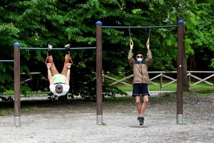 Dos personas con máscaras faciales hacen ejercicios en el parque Sempione, en Milán, Italia (Reuters/ Flavio Lo Scalzo/ File Photo)