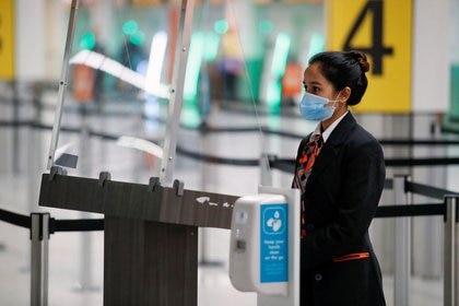 Una trabajadora del aeropuerto de Gatwick, en medio del brote de coronavirus, en Gatwick, Reino Unido,