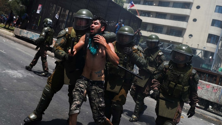 Un manifestante es detenido por la policía en la cuarta semana de protestas en Chile (REUTERS/Pilar Olivares)