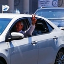 President-elect Alberto Fernandez flashes a victory sign as he drives to Congress to take the oath of office in Buenos Aires, Argentina, Tuesday, Dec. 10, 2019. (AP Photo/Marcos Brindicci)