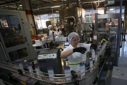 Una trabajadora inspecciona las botellas de alcohol de la fábrica de  L'Oreal Brasil (REUTERS/Rahel Patrasso)