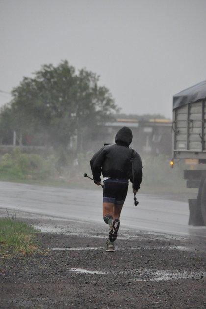 Tibaldi corriendo bajo la lluvia al costado de la ruta, durante los primeros días de la expedición