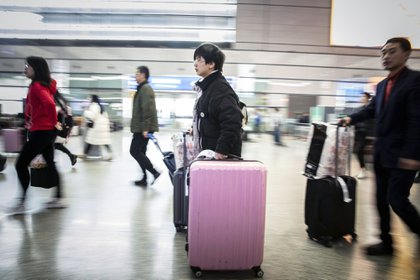 Travelers carry their luggage through the main hall of the Shanghai Hongqiao Railway Station in Shanghai, China, on Wednesday, Jan. 30, 2019. Chinese New Year is an annual ritual of family reunification and overindulgence. The scale of the migration is astounding: While some 54 million Americans undertake a significant journey for Thanksgiving, Chinese citizens will rack up about 3 billion trips during this year's travel-fest.