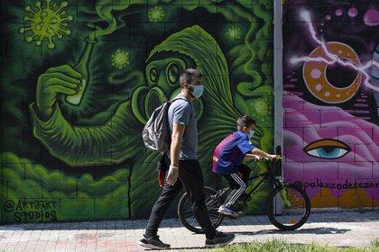 Un niño pasea en bicicleta junto a su padre en una calle de Barcelona, España.