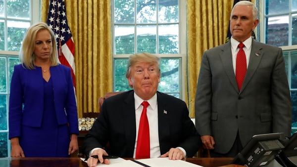 El presidente de EE. UU. Donald Trump firma una orden ejecutiva sobre política de inmigración conla secretaria de Seguridad Nacional, Kirstjen Nielsen, y el vicepresidente Mike Pence, en la Oficina Oval en la Casa Blanca en Washington, EEUU, 20 de junio de 2018 (Reuters)