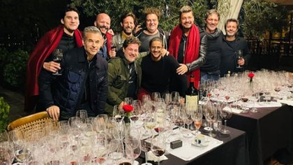 The Tinelli, in red poncho, and their friends during a tasting