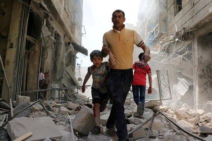Un hombre sirio y un niño evacúan el área luego de bombardeos en el barrio de Hayy Aqyul, en Alepo. Ameer Alhalbi, Agence France-Presse