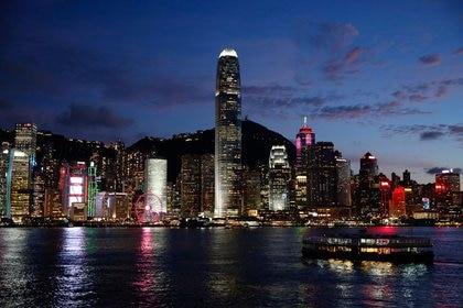 FOTO DE ARCHIVO: Un barco de la compañía Ferry Boat navega por el puerto de Victoria Harbour frente a varios rascacielos en la noche de Hong Kong, China, el 29 de junio de 2020. REUTERS/Tyrone Siu