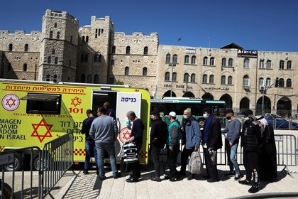 La gente hace cola para vacunarse contra la enfermedad del coronavirus (COVID-19) en un vehículo de vacunación móvil, en Jerusalén el 26 de febrero de 2021. REUTERS/Ammar Awad