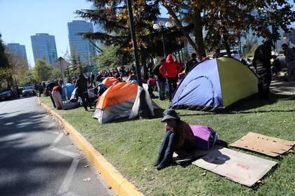 Ciudadanos bolivianos permanecen instalados en las afueras del consulado de su país en Santiago, Chile. el 28 de abril (REUTERS/Iván Alvarado)