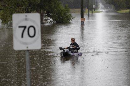 Un hombre en una canoa en una calle inudada de Londonderry, en las afueras de Sydney (AP Photo/Mark Baker)
