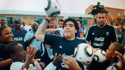 Diego repartiendo pelotas de fútbol con Walter en uno de sus viajes
