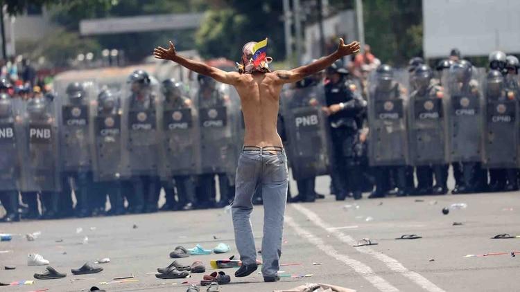 Un manifestante se enfrenta a la policía que bloquea el paso de la ayuda humanitaria en la frontera entre Colombia y Venezuela (Reuters)