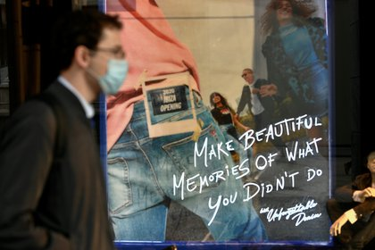 Un hombre con un barbijo pasa frente a una tienda en Milán  (REUTERS/Flavio Lo Scalzo)