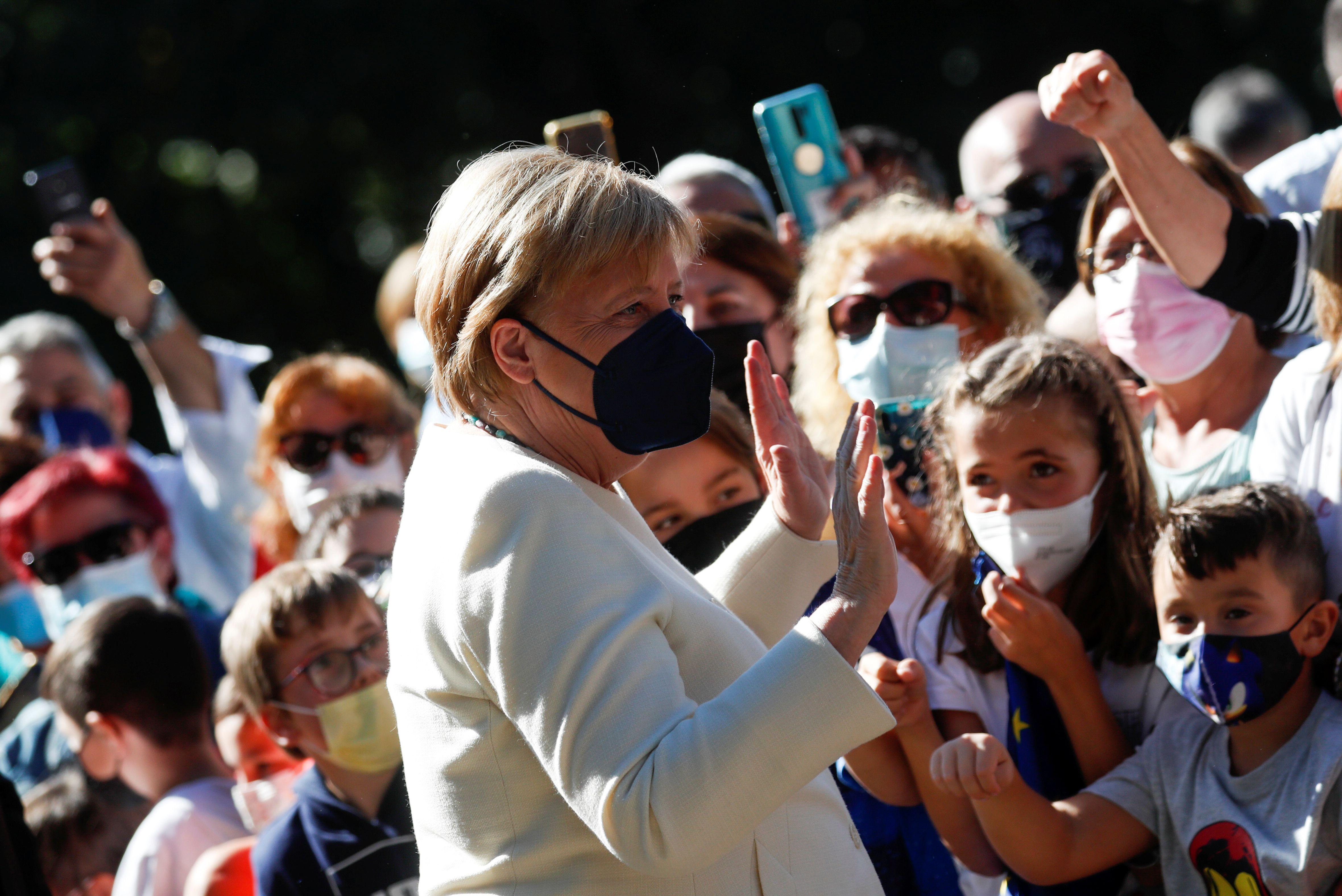 """La canciller alemana Angela Merkel saluda a las personas a su llegada para recibir el """"Premio Europeo Carlos V"""" en el Monasterio de Yuste, en la región occidental española de Cáceres, el 14 de octubre de 2021. REUTERS / Susana Vera"""