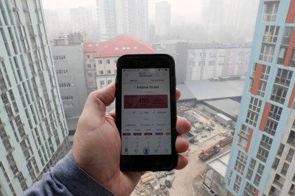 Foto de archivo de un hombre midiendo la calidad del aire en Kiev con una app en su teléfono celular. Abr 18, 2020. REUTERS/Gleb Garanich