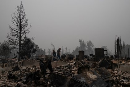 Una pareja revisa los escombros de su casa en Talent, Oregon (Reuters)