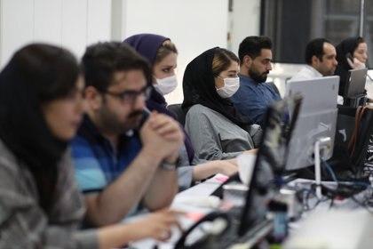 Empleados de una empresa financiera usan máscaras protectoras monitorean los precios de las acciones en Teherán, Irán, el 12 de mayo de 2020 (WANA / Agencia de Noticias de Asia Occidental /Ali Khara vía REUTERS)