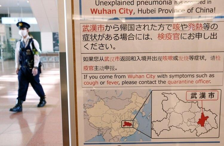 Un policía con una máscara pasa junto a un aviso de cuarentena sobre el brote de coronavirus en Wuhan, China, en una sala de llegadas del aeropuerto de Haneda en Tokio, Japón, el 20 de enero de 2020. (REUTERS / Kim Kyung-Hoon)