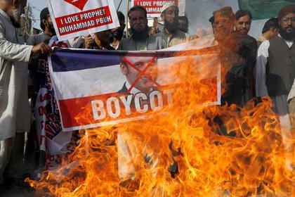 Manifestantes queman una pancarta con la foto de Macron en Karachi, Pakistán (Reuters/ Akhtar Soomro)