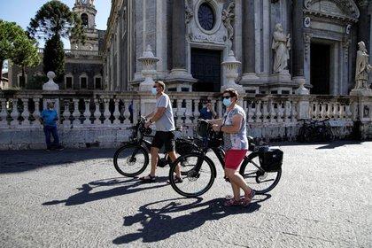 Dos personas con mascarilla caminan con sus bicicletas por una calle tras la imposición de la obligatoriedad de llevar mascarilla a todas horas en espacios abiertos en Sicilia para contener la expansión de la COVID-19, en Catania, Italia, el 30 de septiembre de 2020. REUTERS/Antonio Parrinello