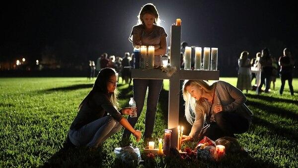 Miles de personas sostienen velas durante una vigilia por las víctimas de la balacera de la Marjory Stoneman Douglas High School en Parkland, Florida (AFP)