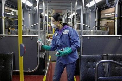 Una trabajadora de mantenimiento de vehículos limpia un autobús con un desinfectante en Seattle, Washington, EEUU. 2 de marzo de 2020.  REUTERS/Jason Redmond