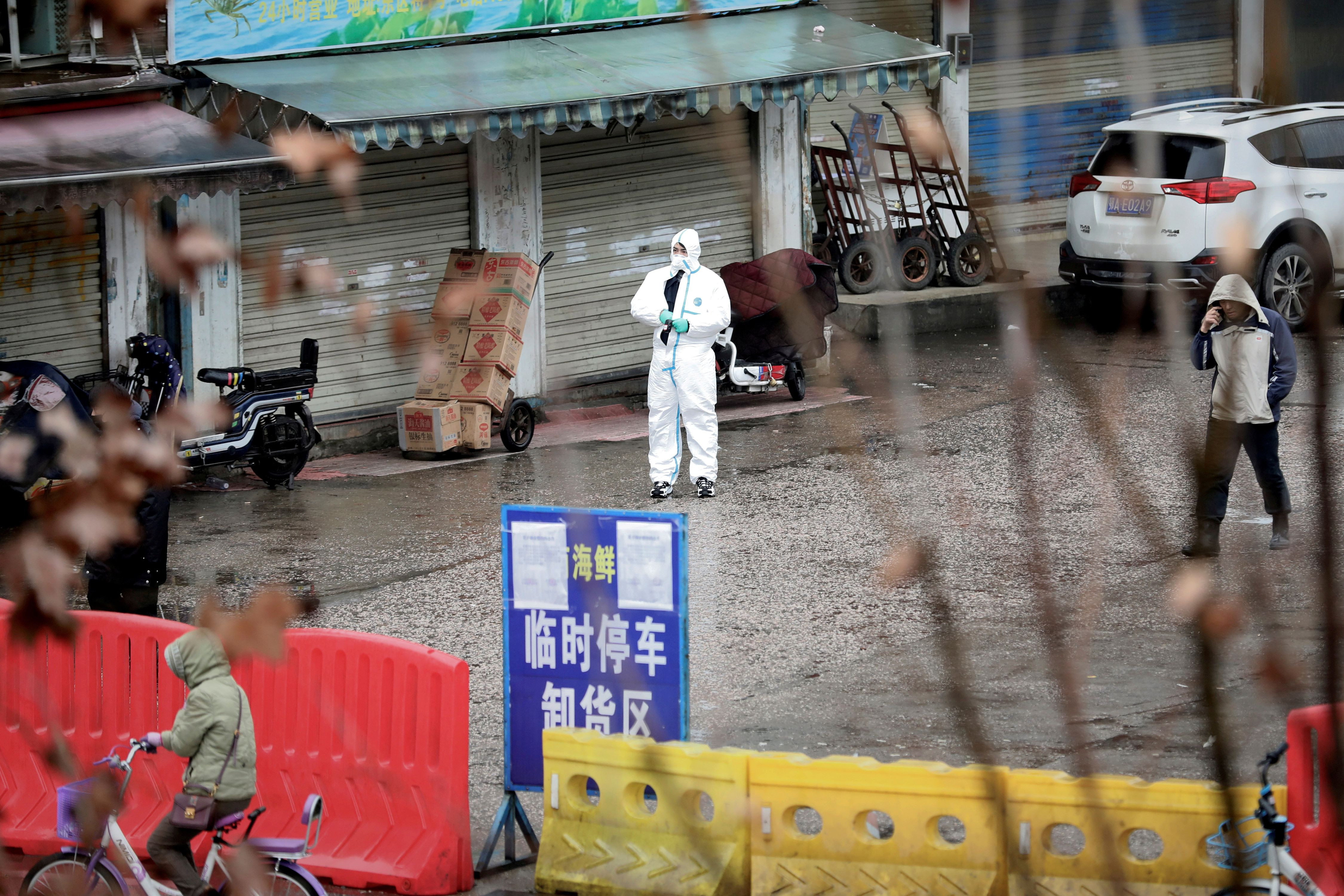 FILE PHOTO: A worker in a protective suit is seen at the closed seafood market in Wuhan, Hubei province, China January 10, 2020. Picture taken January 10, 2020. REUTERS/Stringer/File Photo