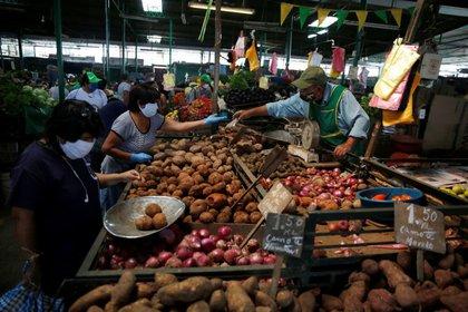 Una mujer compra papas en un mercado de Lima. Mayo, 2020. REUTERS/Sebastian Castañeda