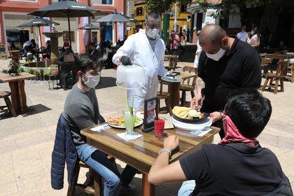 Un grupo de personas consume alimentos al aire libre en la plaza del Chorro de Quevedo en Bogotá; (Colombia). EFE/ Carlos Ortega/Archivo