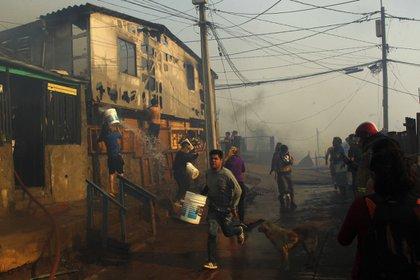 Vecinos ayudan a combatir un incendio forestal en el sector de Playa Ancha en la ciudad de Valparaíso (Chile) que afectó a viviendas y vecinos del sector (EFE)