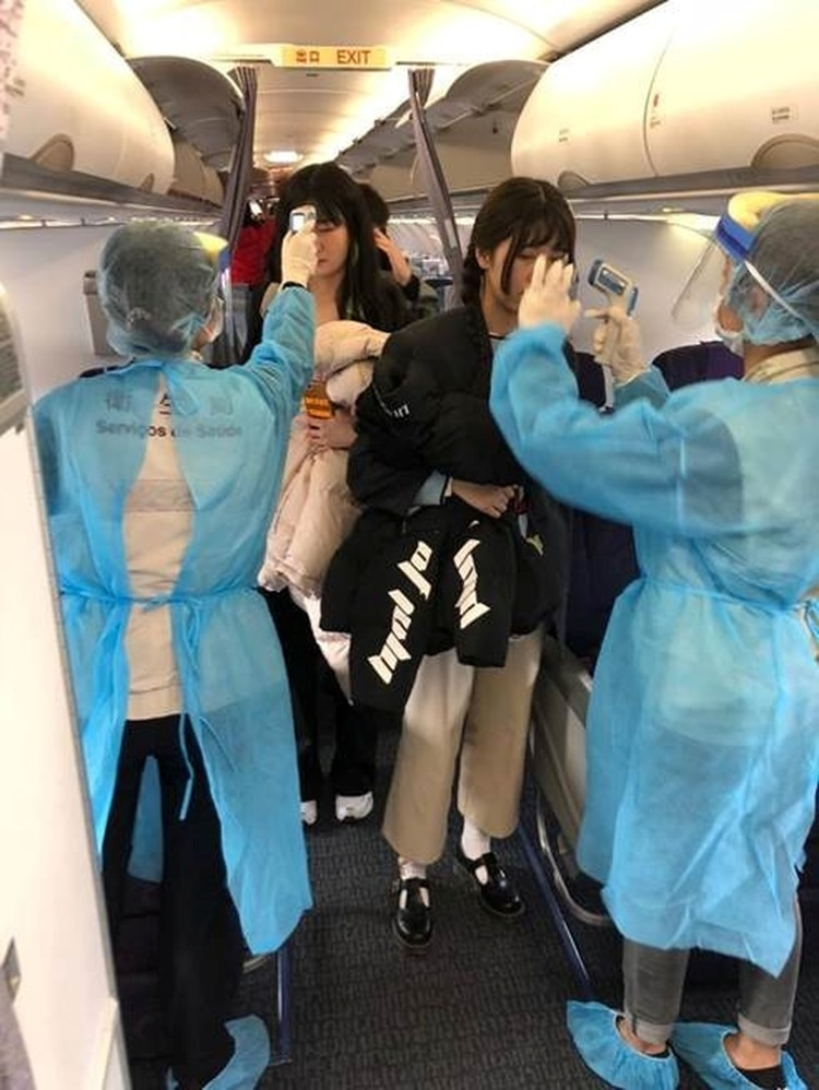 Oficiales revisan la temperatura de los pasajeros de un vuelo entre Wuhan y Macao (Reuters)