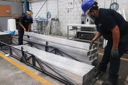 MEX2090. CIUDAD DE MÉXICO (MÉXICO),04/06/2020.- Empleados de la fábrica de Aluminio Extral, durante una jornada de trabajo, el 3 de junio de 2020, en Ciudad de México. Las empresas mexicanas del aluminio, que mueven unos 15.000 millones de dólares al año, han comenzado a reactivarse esta semana para apoyar a sus clientes esenciales de los sectores automotriz, alimentación y medicina. EFE/José Pazos