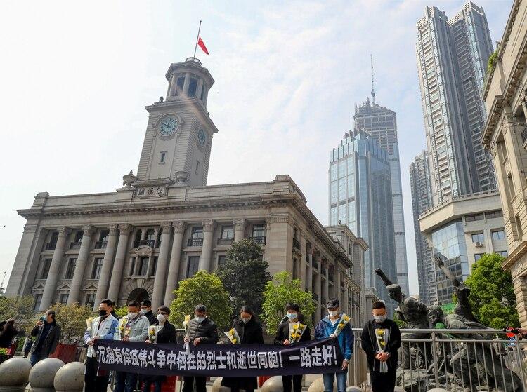 Una ceremonia en silencio de homenaje a los fallecidos frente a la aduana de Hankou en Wuhan, donde la bandera china está izada a meda asta.