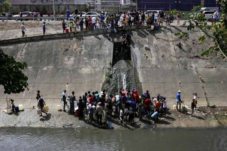 La gente recolecta agua de un canal de aguas residuales en el río Guaire en Caracas el 11 de marzo de 2019, mientras un apagón masivo continúa afectando algunas áreas del país (AFP)