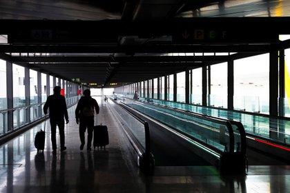 Dos pasajeros cruzan una de las terminales del Aeropuerto Adolfo Suárez Madrid-Baraja. EFE/Emilio Naranjo/Archivo