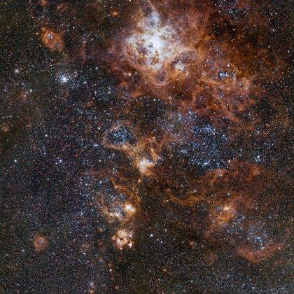 El proyecto Qubic intenta encontrar por primera vez en la radiación de fondo cósmico el rastro de las ondas gravitacionales primordiales que tuvieron lugar luego de la primera explosión del universo. En la foto, se observa la nebulosa de la Tarántula, que forma parte de la Gran Nube de Magallanes, una galaxia cercana a la Vía Láctea (ESO)