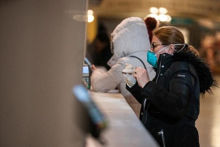 Una mujer con una mascarilla protectora utiliza un cajero automático en el terminal central de Manhattan. Marzo 16, 2020. REUTERS/Jeenah Moon