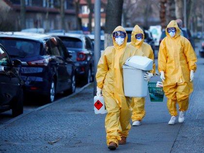 Un equipo médico camina hacia el centro de pruebas del COVID-19 instalado fuera de la oficina de una tienda de campaña en el distrito Reinickendorf de Berlín, Alemania, el 23 de marzo de 2020. (Foto: Reuters/Fabrizio Bensch)