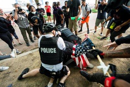 En Washington DC se produjo una manifestación por la tarde de este viernes, donde oficiales de la policía arrestan a un participante que fue reducido contra el piso (EFE/EPA/JIM LO SCALZO)