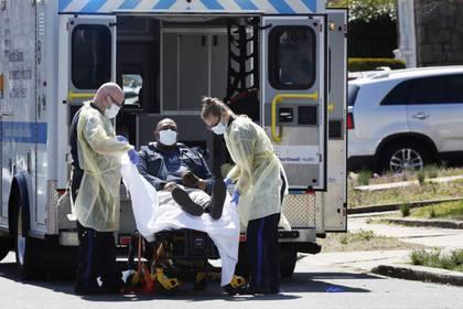 Técnicos de emergencias médicas llevan a un paciente con enfermedad por coronavirus (COVID-19) a una ambulancia mientras usan equipo de protección en la ciudad de Nueva York. 26 de marzo de 2020.  REUTERS/Stefan Jeremiah