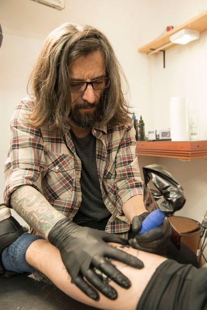 El tatuador, en plena acción